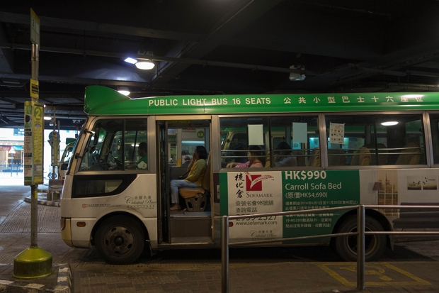 A woman sits in her seat, waiting for the green minibus #2 to depart.