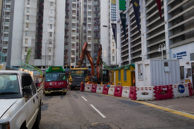 A green minibus squeezes through Tak Ting Street, which has been narrowed by construction road blocks near the Whampoa Gardens bus terminus.