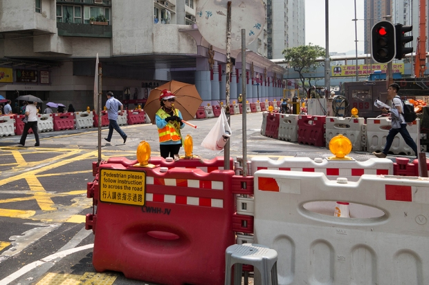 A crossing guard directs pedestrians across the large, busy intersection at Hung Hom Road and Tak On Street. The traffic lights change depending on where the road blocks are placed.