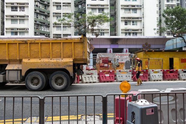 A construction worker signals a large truck to back up on Hung Hom Road.