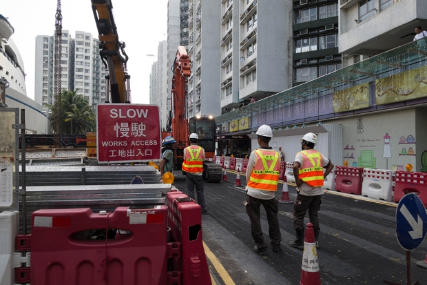 Construction workers watch as a machine is driven down a road in Whampoa Gardens.