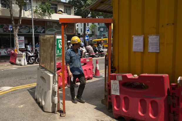 A construction worker exits the site on Tak On and Man Tai Streets for his break.